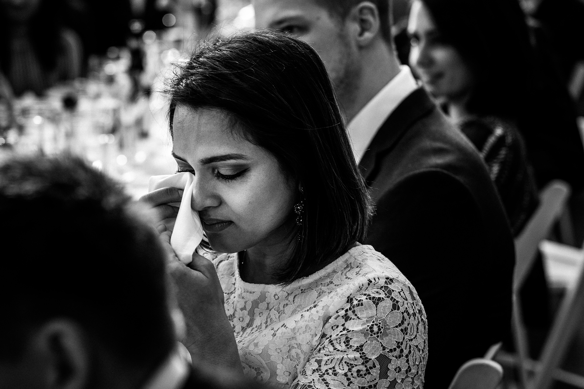 A guest drying her eyes with a napkin as she cries during the speeches