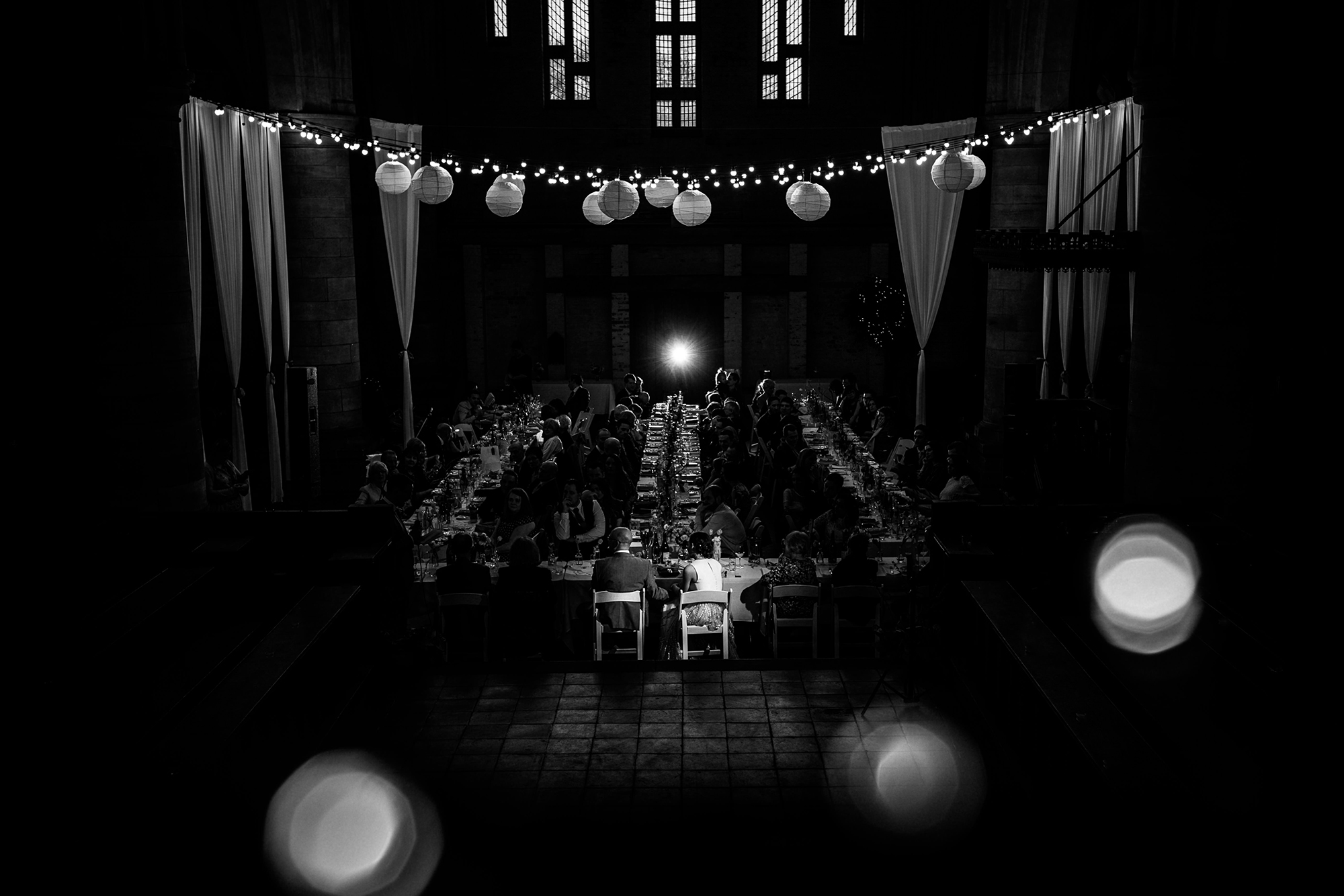 A black and white shot of a wedding reception as everyone eats their meal