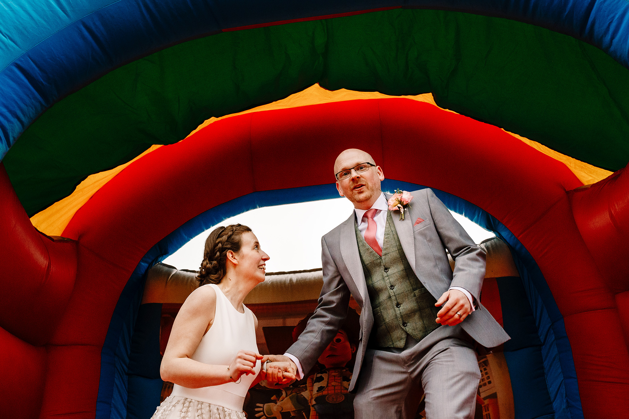 A BRIDE AND GROOM JUMPING ON A BOUNCY CASTLE