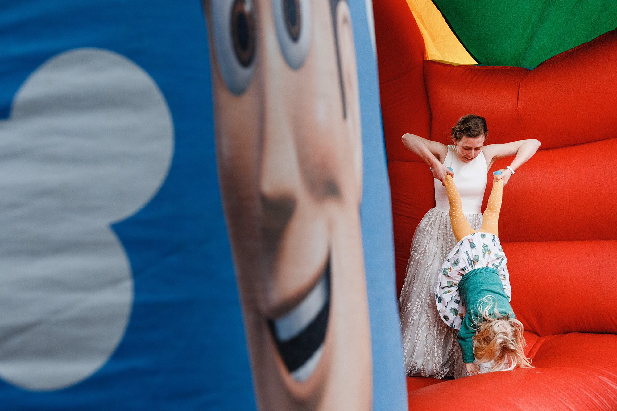 A bride holding a child upside down on a bouncy castle