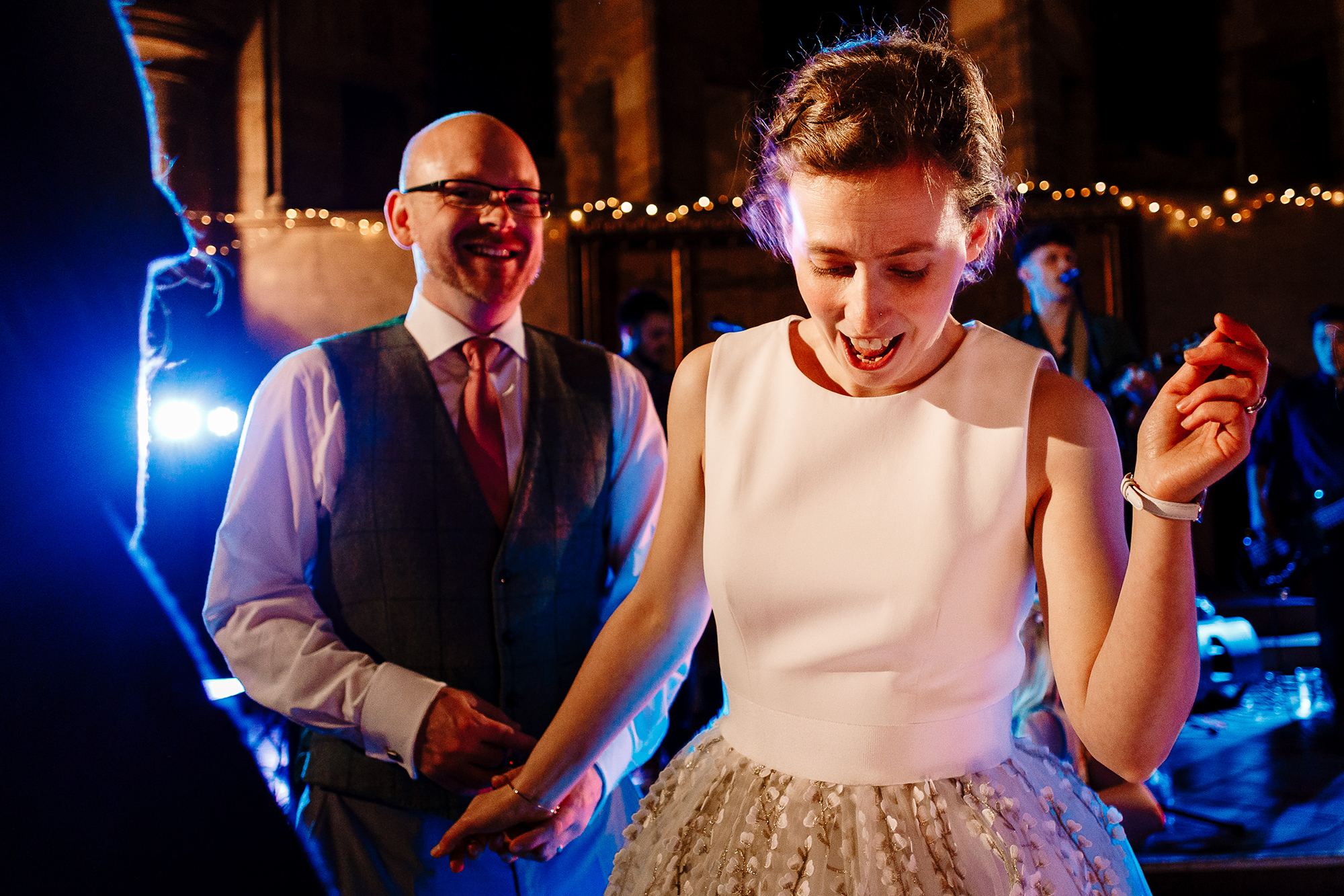 A bride dancing and smiling while a groom smiles behind her