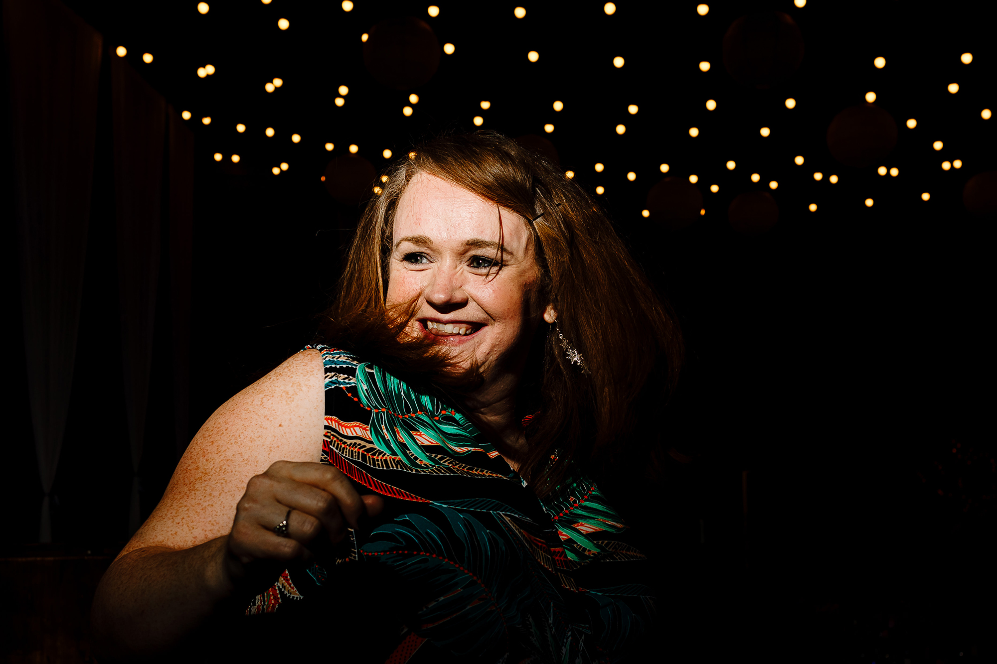 A guest smiling and dancing at a wedding