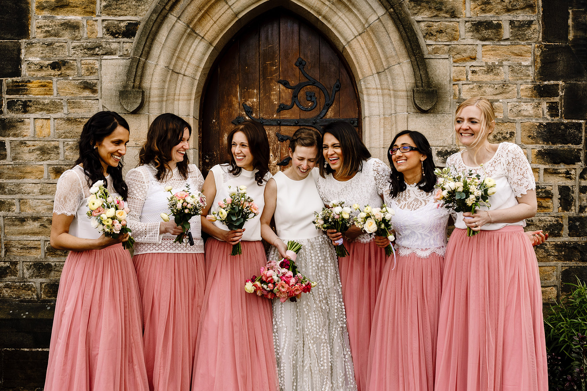 A bride and er six bridesmaids laughing