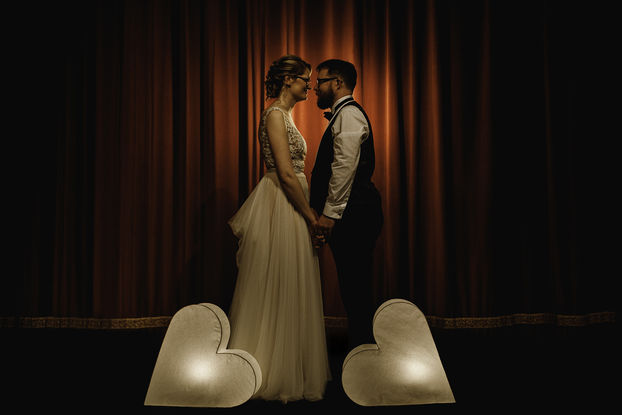 A bride and groom standing by a red theatre curtain holding hands with two heart shaped lights at either side of them