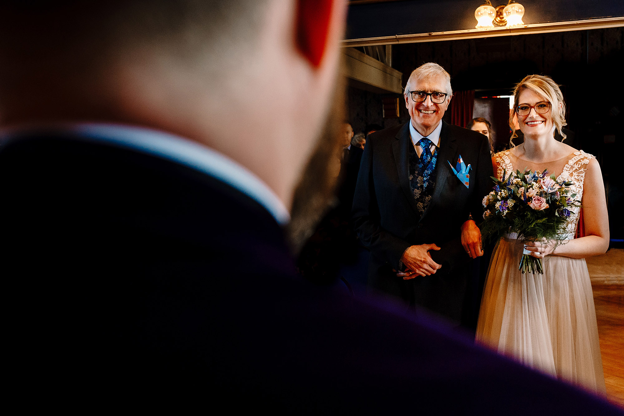 A shot from behind the groom's shoulder of a bride walking towards him with her father as they both smile
