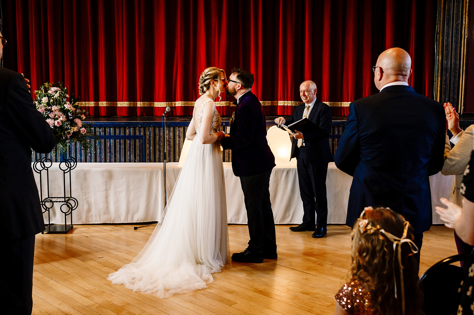 A bride and groom having their first kiss in front of the stage at Guiseley Theatre