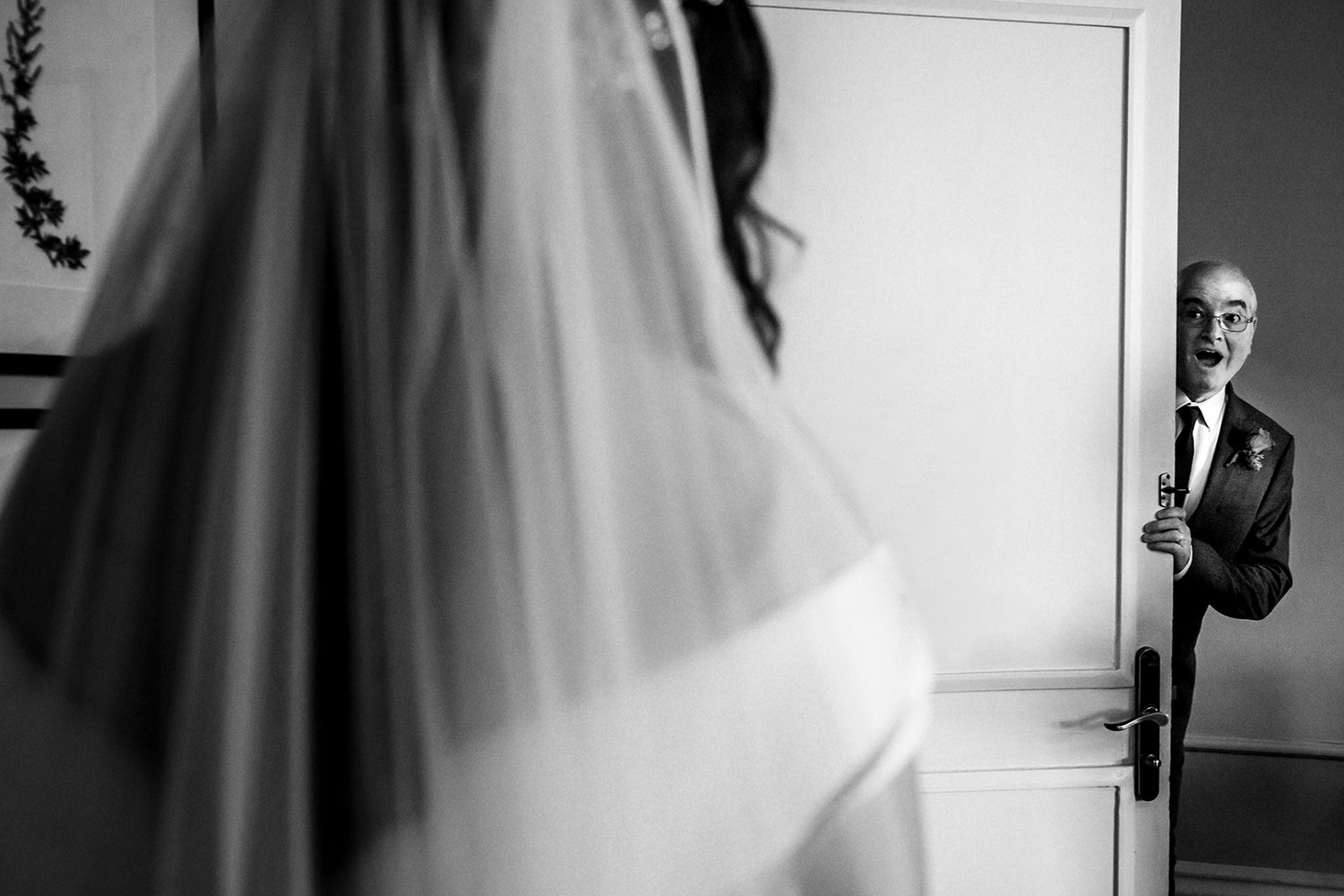 father of the bride peeking round the door looking surprised at seeing his daughter in her wedding dress