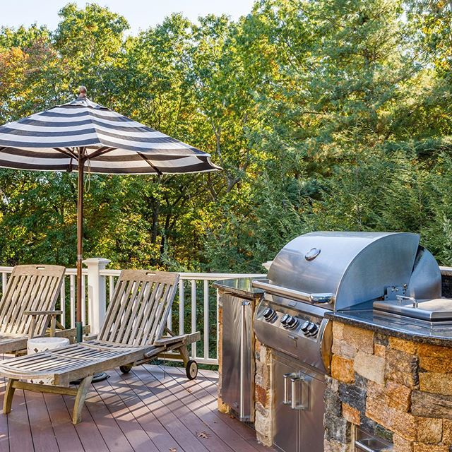 We built this outdoor kitchen for one of our favorite clients — that grill works hard and there's almost always a lovely bottle of gin chilling in the ice tub.  #outdoorkitchen #designandbuild #newengland #builtingrill #medfield #ginandtonic