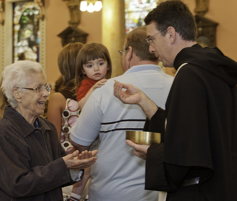 Fr. Joe Farrell, OSA Distrbutes Communion.jpg
