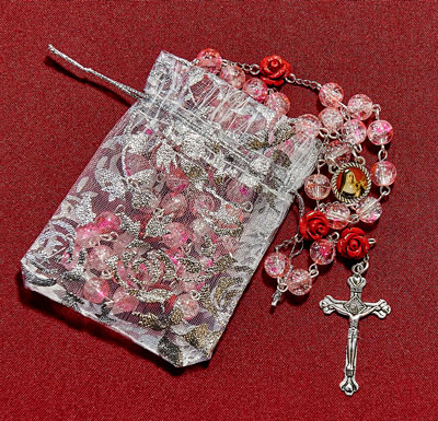 Pink rosary with rose Our Father beads and Saint Rita centerpiece, elegantly wrapped in a rose patterned gift pouch.