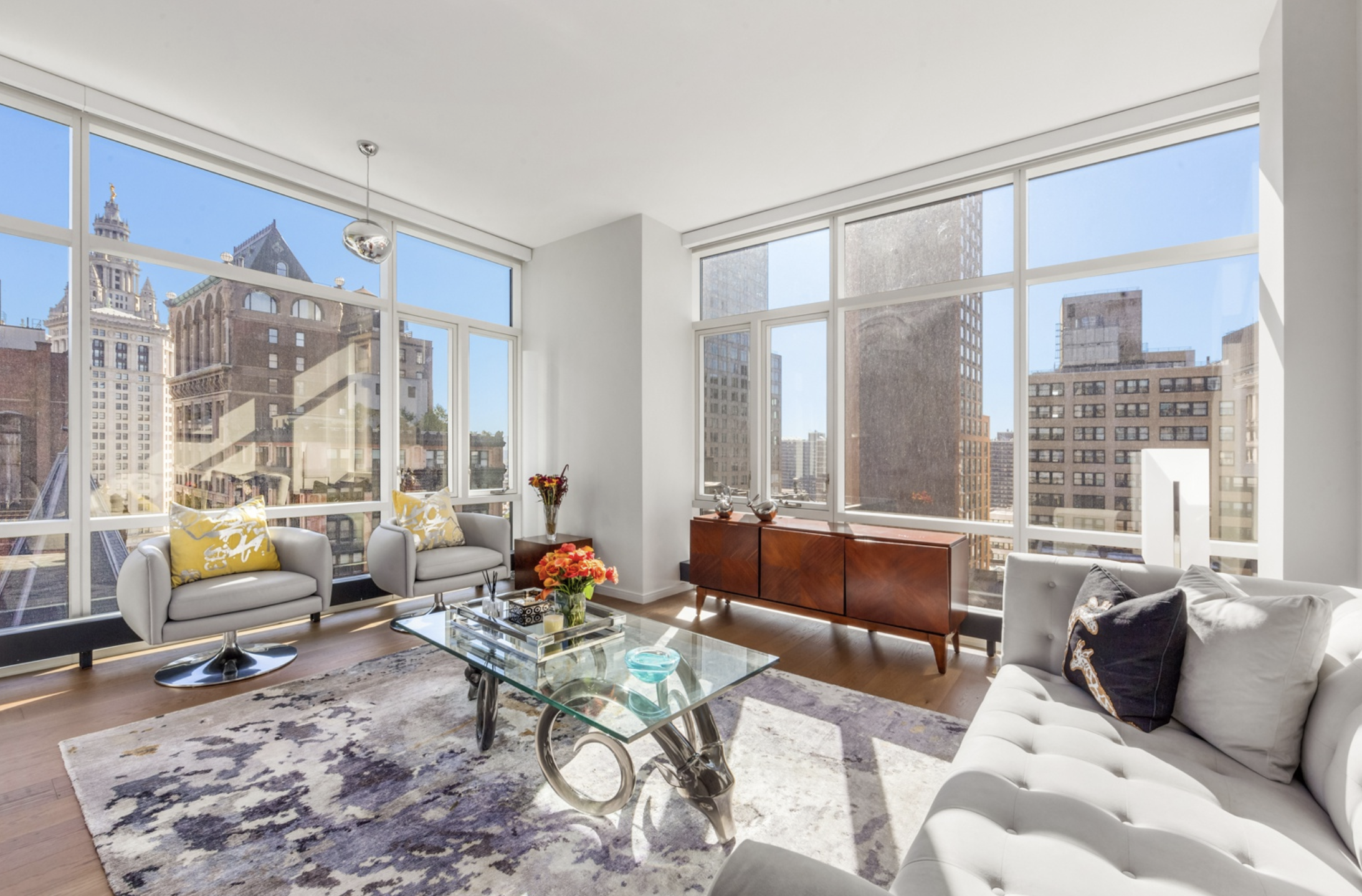 5 BEEKMAN STREET, 18B - $1,685,000 // 1 Beds // 1 Baths // 855 SQFTAn elegant corner condo boasting charming views of lower Manhattan, this pristine home is a portrait of classic city living. Features of this 855 sq. ft. apartment include gorgeous hardwood floors, stunning wall-to-wall floor-to-ceiling windows, motorized shades, northern and eastern exposure, central heating and cooling, and a convenient in-unit washer/dryer.