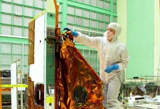 Aleks Bugunovic's reflection as she works on a Multi-Layer Insulation blanket at Aerothreads