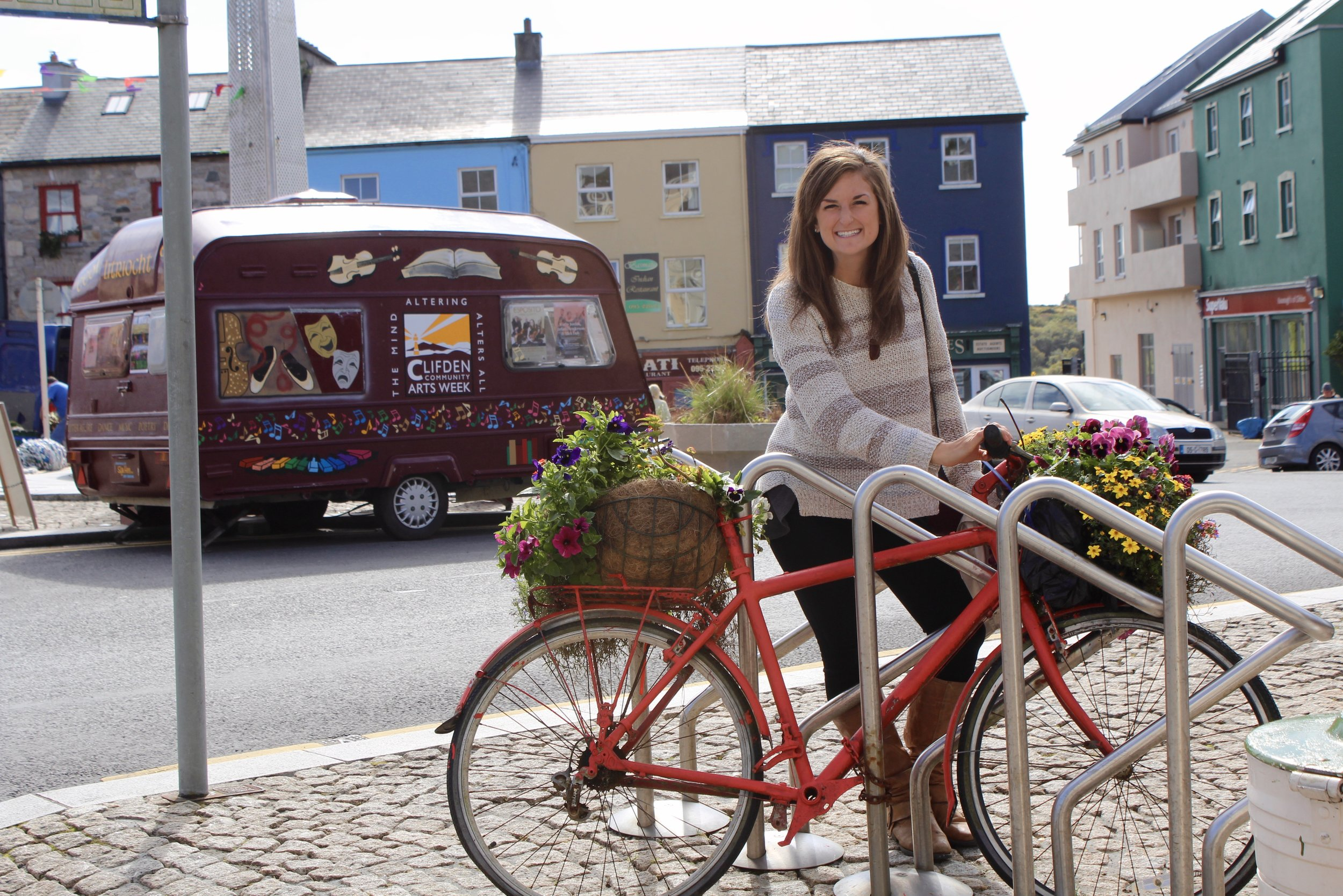 Me and a bike with flower-filled baskets in Clifden, Connemara. When it's an option, I much prefer biking or walking to motorized vehicles.