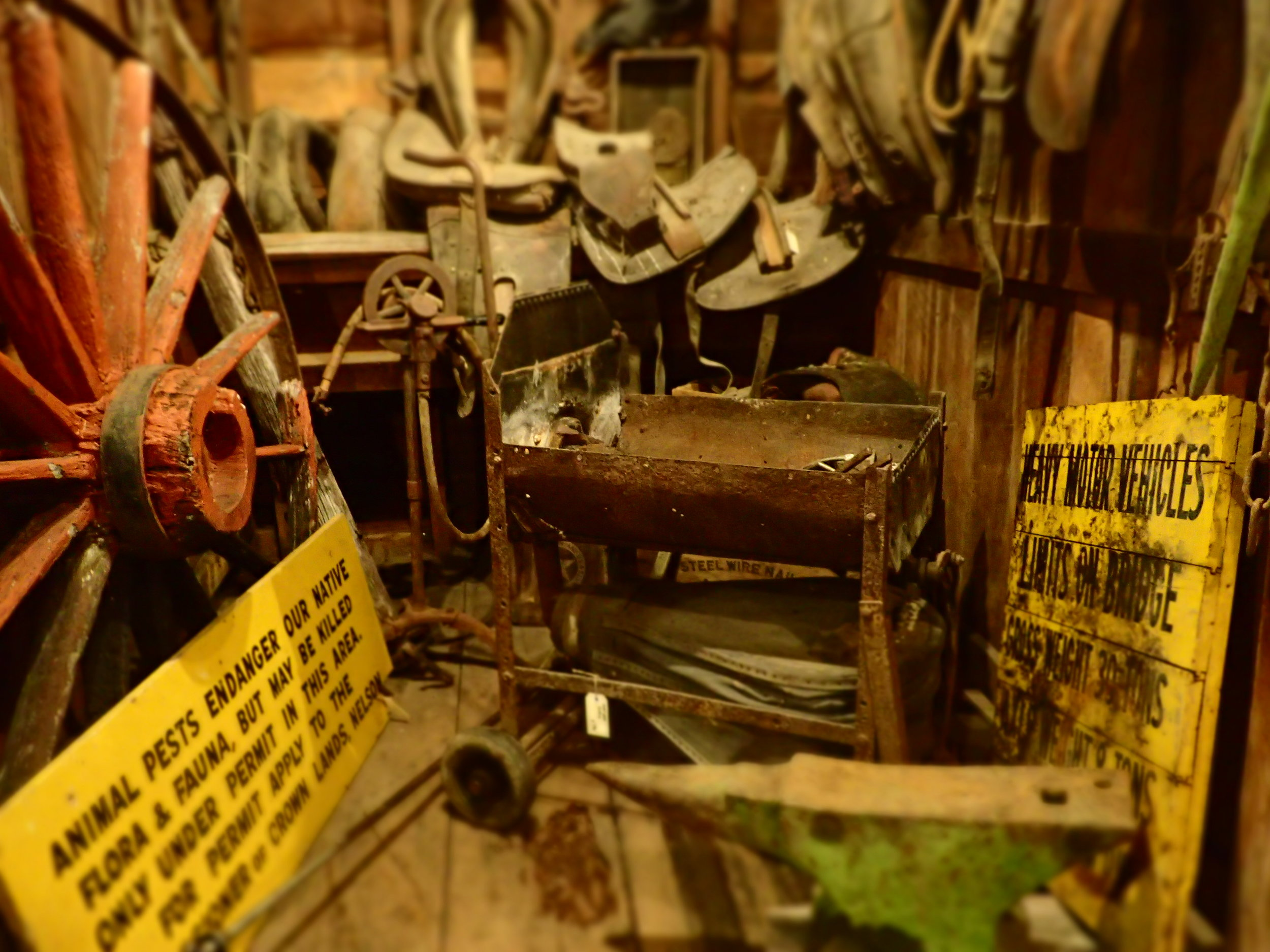 Raw and unrestored blacksmith's tools & horse cart gear in the horse box, hand operated forge and anvil.