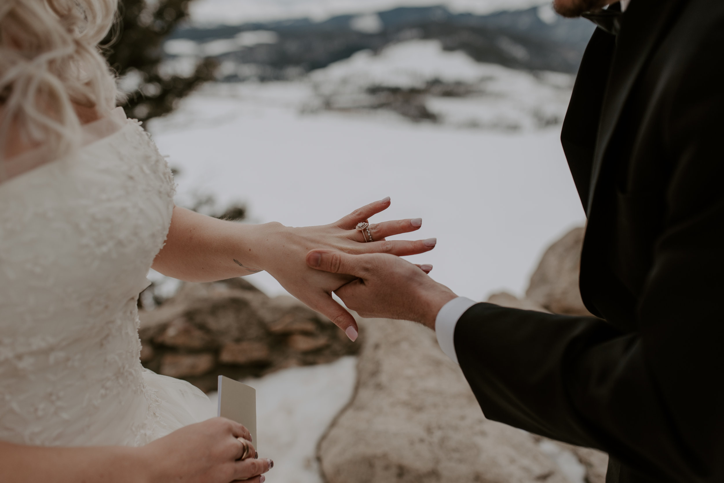 Groom putting on the bride's ring at a winter elopement at Sapphire Point in Dillon, Colorado. Denver, Colorado based elopement and wedding photographer.