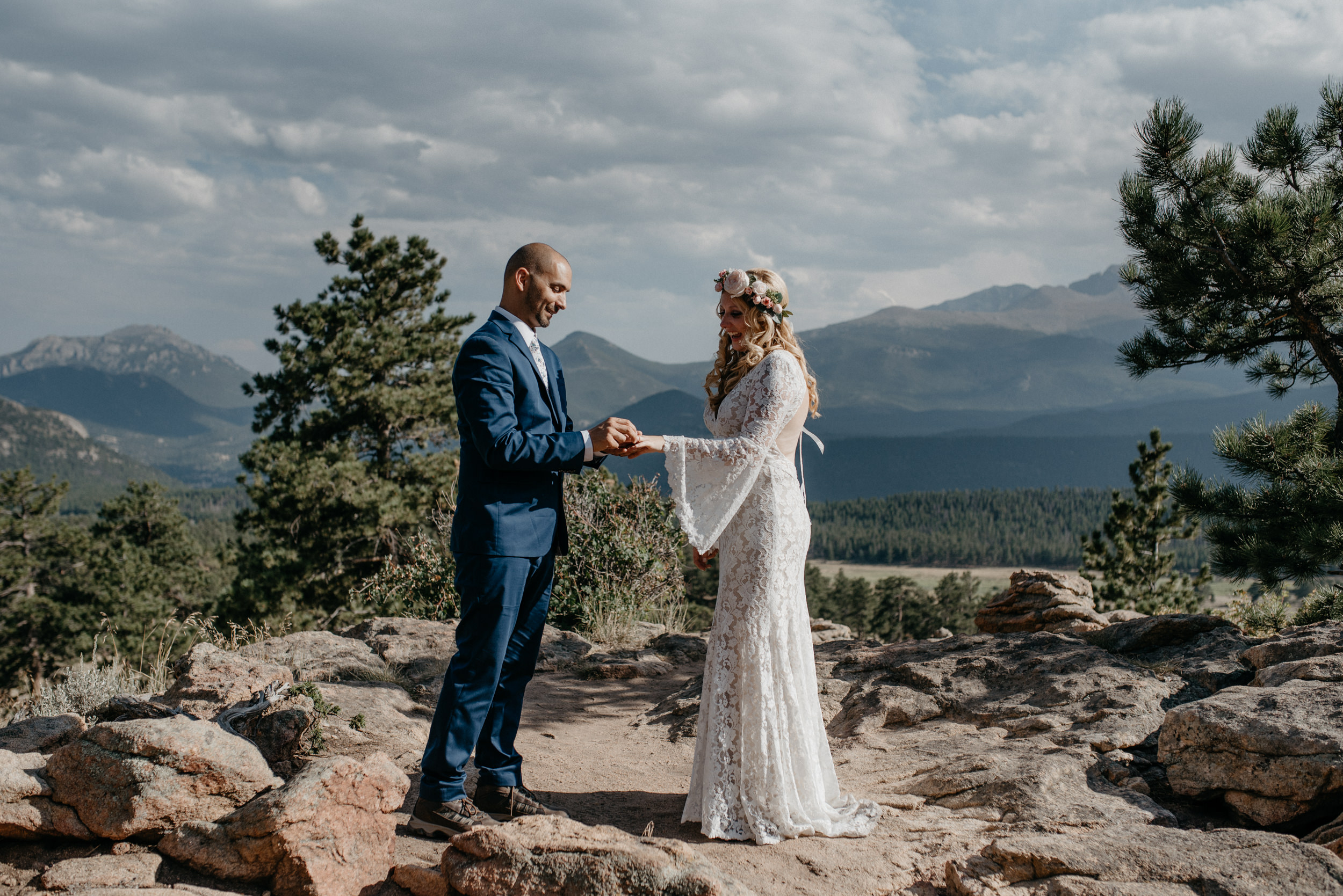 Groom putting on ring at intimate ceremony in Rocky Mountain National Park at 3M curve.