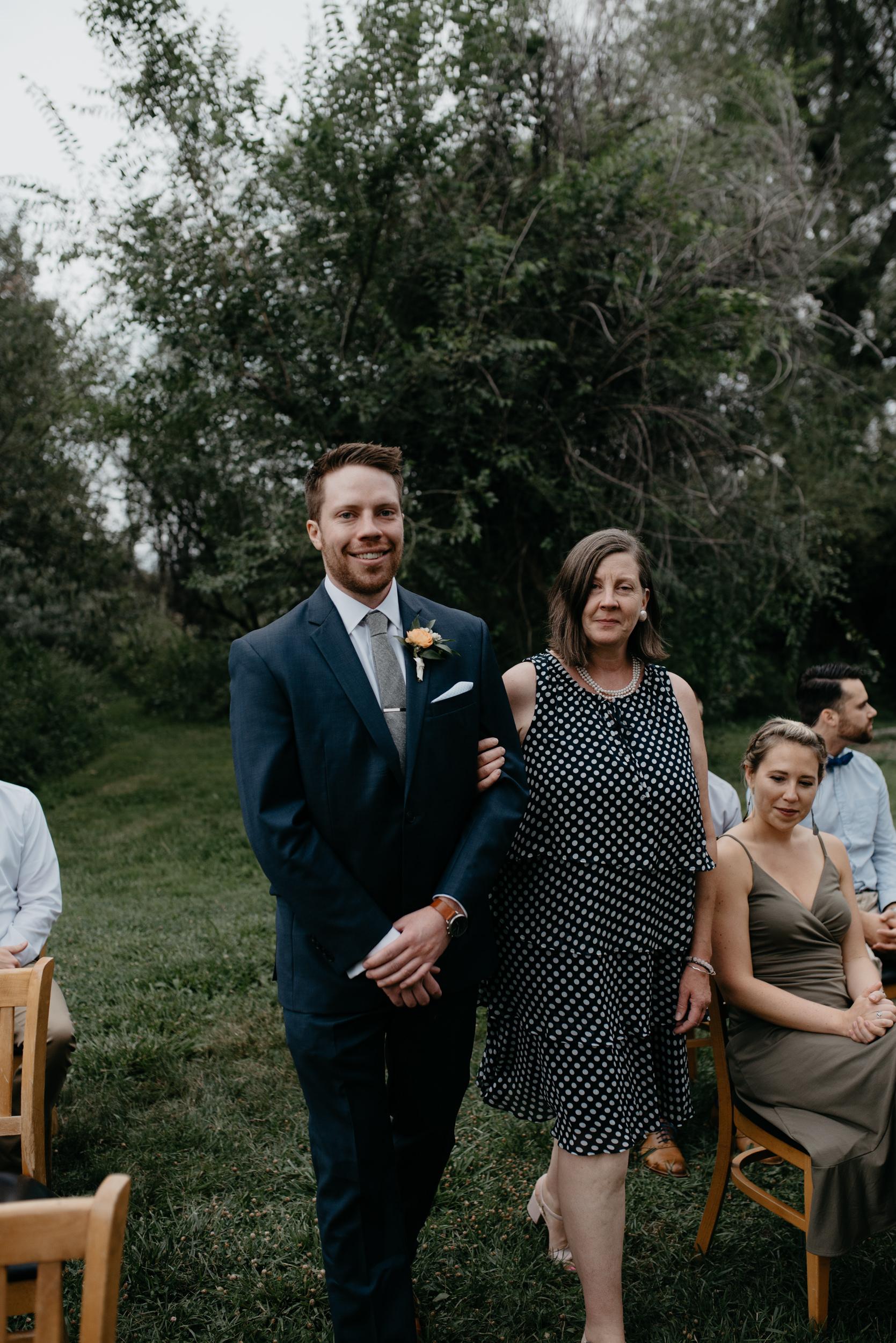 Groom and mom walking down isle at Three Leaf Farm wedding in Boulder, Colorado.