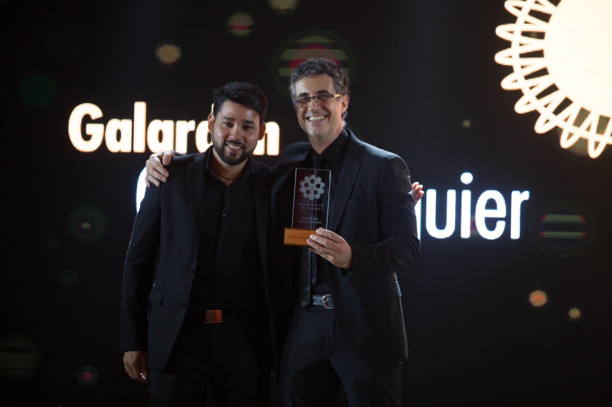 Juan Carlos Maneglia recibiendo el galardon de parte de Celso Franco, quien interpretara el papel protagónico de Victor en el film 7 cajas.