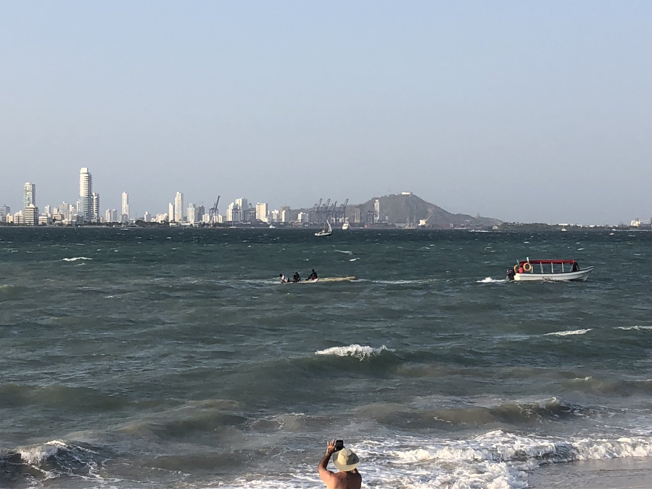 The capsized boat being towed into shore.