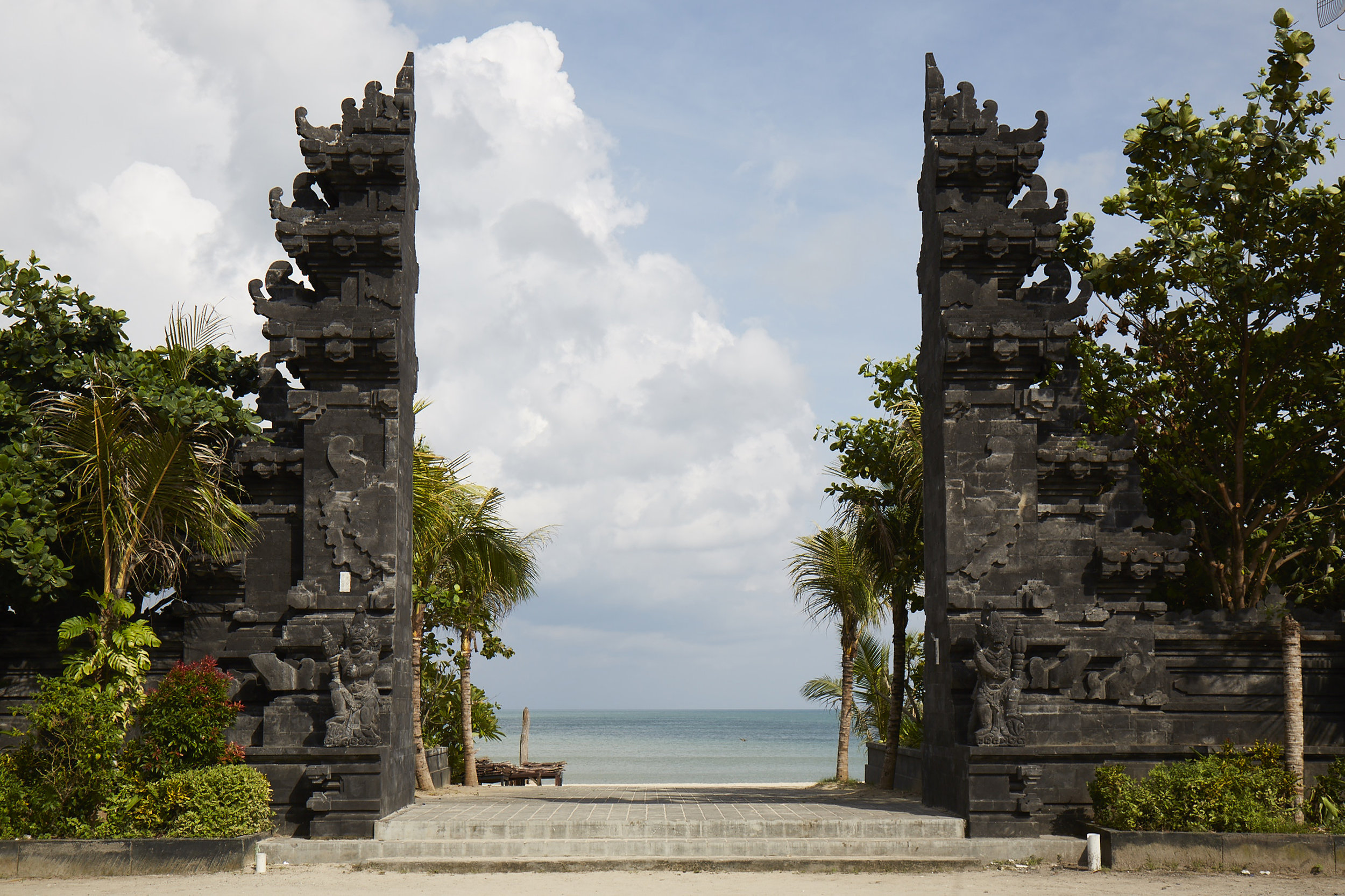 """View from my Motorbike at Jimbaran Beach, Bali, Indonesia. I was told by a Balinese Hindu """"HolyMan' this type of gate represents a holy place, on top of the mountain. You have the appearance of walking over the top and seeing the view below. Being on top of everything (the world...spiritually)."""