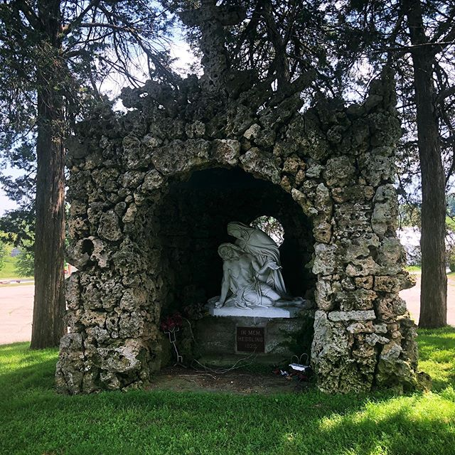 This is my family's grotto located in the cemetery where several members of my family are buried.  _ Our grotto depicts the pietà, where Mary is cradling the body of Jesus after the crucifixion.  _ As a spiritualist and a medium, much of the teachings and doctrine of Catholicism do not resonate with me. As a feeling human who has a complicated past with the religion, much of the accepted social practices within the faith and the behavior of its leaders do not resonate. But, I do still find peace in some of the buildings that the Church and it's believers have built, including the series of grottos at this cemetery. _ Also as a spiritualist and medium, I do not believe my family members who are now in Spirit are hanging out at their human gravesites. But I know that if I feel the need to visit their graves and stand where we buried their human bodies so I can connect with them, they will show up for me.  _ And so they showed up for me today. I felt their presence. I shared feelings and fears I've been keeping inside. I cried. I asked for their guidance and help. I felt heard and acknowledged and loved. So, today ended better than it started.  ____________ I've decided to intentionally share one photo on here each day that I actual took on that day. Latergramming may make my feed more visually appealing and may make my life seem more beautiful and interesting, but sharing one snapshot of my day more accurately reflects this journey that I am on and this life that I am living.  _ So here is one moment from my life on July 14, 2019 and one glimpse into this intentional journey of healing and rebellion.