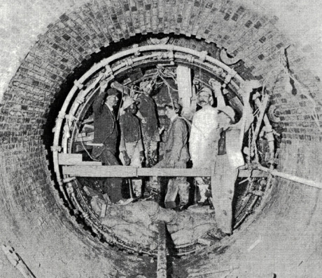 High level sewer, Centre St., Jamaica Plain. Workers are engaged in the construction of a circular tunnel using compressed air tools and a metal shield. From Metropolitan Water and Sewage Board First Annual Report. January 1, 1902.