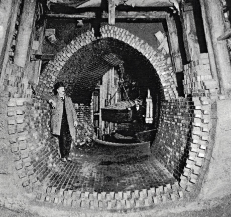 High level sewer construction in sand at Forest Hills, Jamaica Plain. Note bin suspended from overhead crane with trolley used to remove excavated dirt from tunnel. Due to the sandy nature of the soil in this area, wooden beams resting on a foundation provide support for the roadway above. From Metropolitan Water and Sewage Board First Annual Report. January 1, 1902.