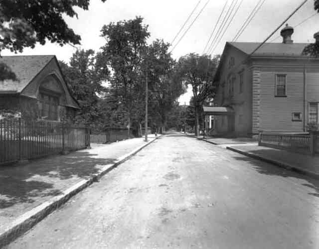 Eliot St. looking from Centre St. towards Hagar St. Eliot Hall, home of the Footlight Club is shown on the right and the parish hall of the First Church on the left.