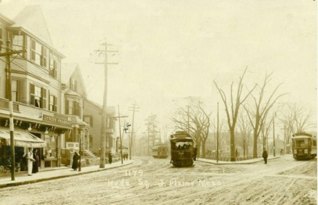 """Three street cars can be seen in this view of the Hyde Square section of Jamaica Plain. The storefront on the left bears a sign, """"Lynch's Pharmacy"""". The camera was positioned near Sherdian St. and Centre looking towards the Square. The two street cars on the left are traveling along Centre St.; one moving towards and the other coming from the direction of Boylston St. Day St. is to the right but can not be seen in this view. No high resolution version of this image is available. Photograph courtesy of Mark Bulger."""