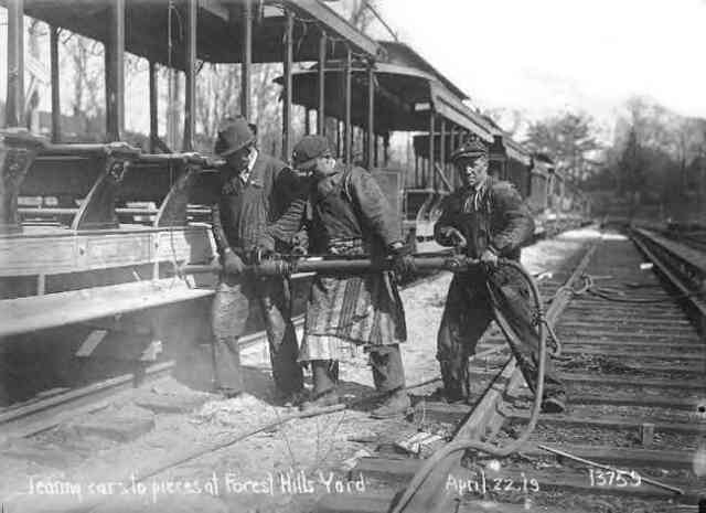 Workmen using a pneumatic impact wrench dismantle open air trolley cars at the Forest Hills yard in 1919. Courtesy of Anthony Sammarco.