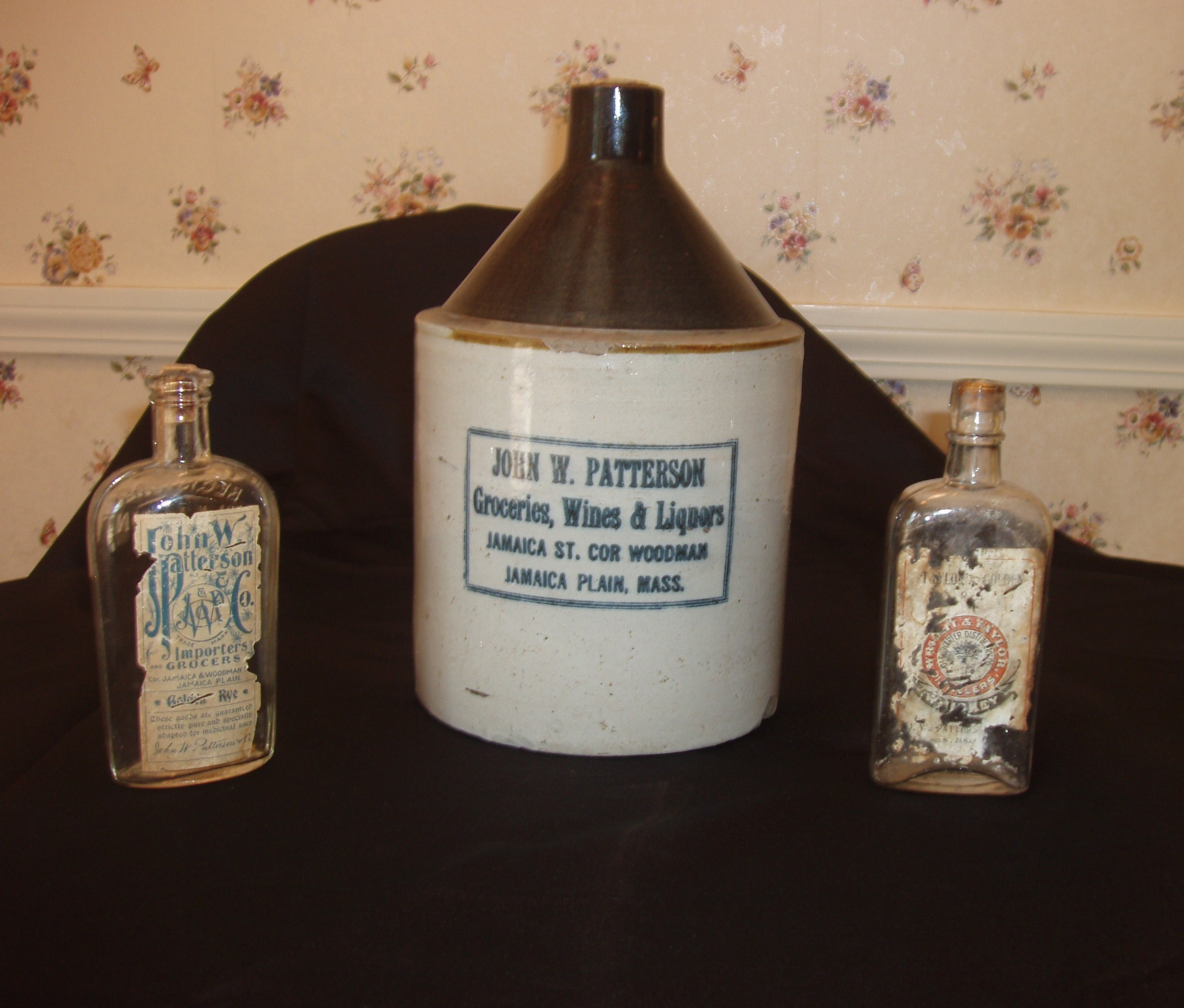 Patterson Market branded whiskey and rye bottles shown on both sides of a Patterson branded jug. Courtesy of the Patterson family.