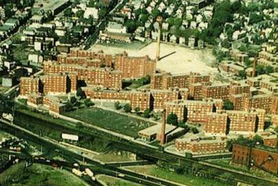 An aerial view of Bromley Heath taken in April 1977.  The Lowell Estate stretched from Centre Street, on the far right, to the ridgeline of the housing cornices. The smokestack in the background is all that remains of the Plant Shoe factory that burned on February 2, 1976.
