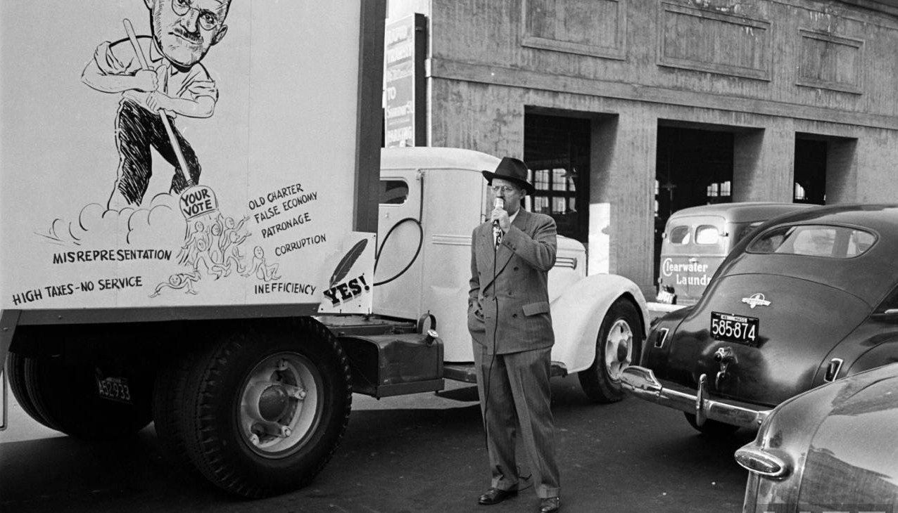 George Oakes, candidate for Boston Mayor campaigns in Jamaica Plain. Oakes was an officer at R.M. Bradley, one of Boston's leading real estate firms. To the right of the candidate is a Clearwater Laundry delivery truck. The laundry stood on Brookside Ave. near Green St. Photograph by Yale Joel/LIFE Magazine.