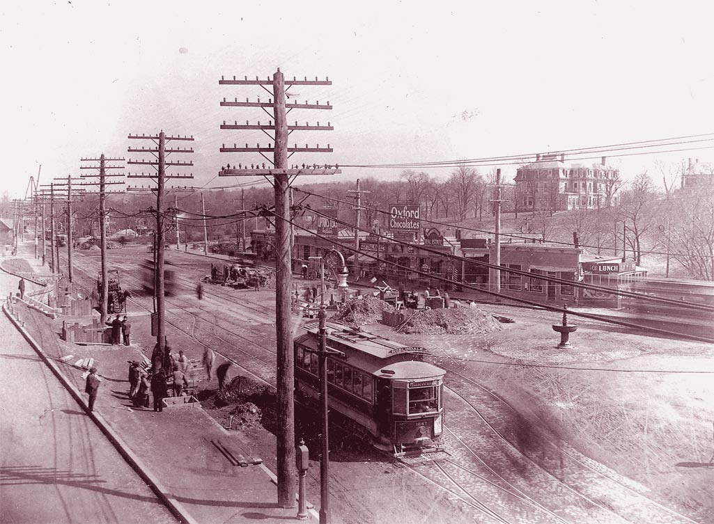 The birth of development across from what is now Forest Hills Station on Washington Street. In this small strip of stores can be seen a lunch counter, a chocolate shop, and other small businesses.  Download photo .