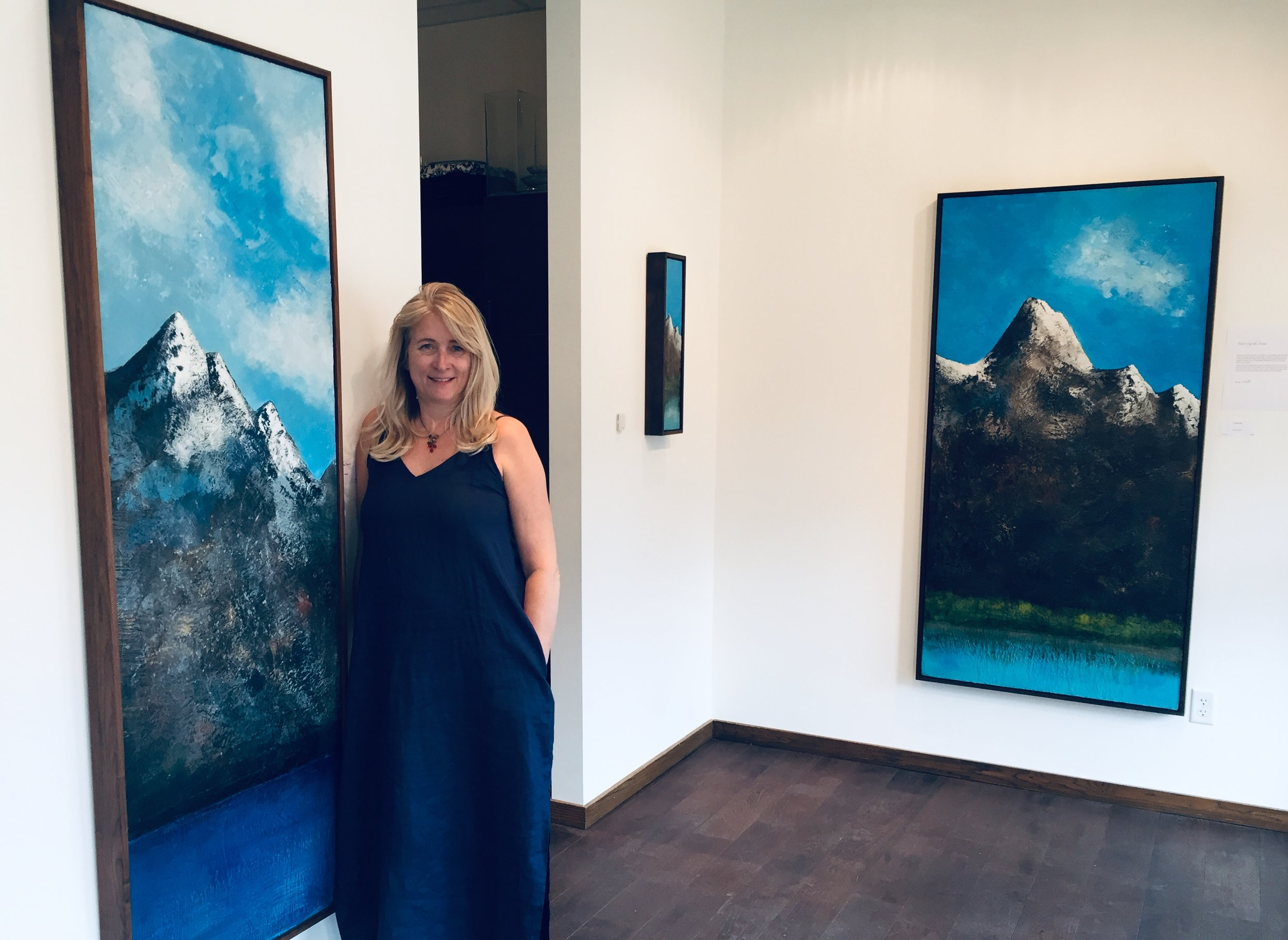 "Susan Wallis at Elevation Gallery during her solo show, ""Traversing the Land"". (Left) Virtuous Stand 24x72 , to the far right; Crescendo 34x69"