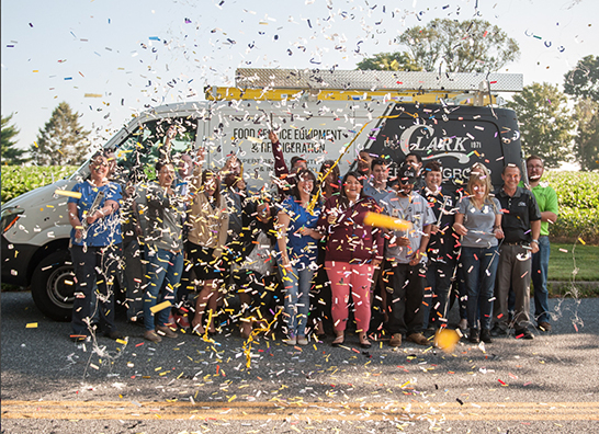 Clark Service Group employees having fun with confetti cannons in front of technician's van.