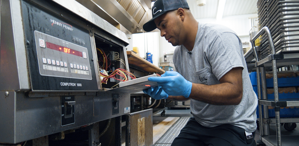 Service technician working on repair of a Henny Penny fryer.