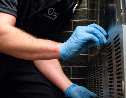 Close up of technician wearing blue gloves while working on the repair and maintenance of a refrigeration unit.