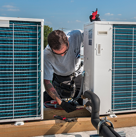 Service technician repairing an Emerson outdoor refrigeration condensing unit.