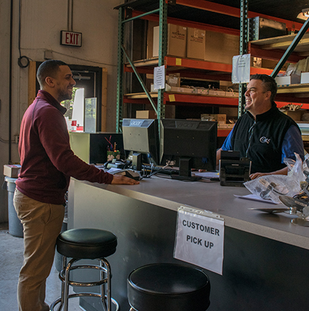 Customer being greeted by friendly employee at the parts counter in the warehouse.
