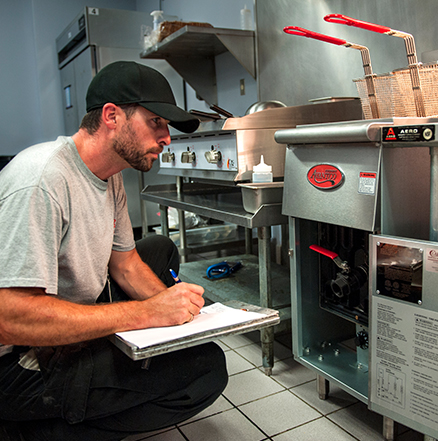 Technician using checklist to diagnose fryer in a commercial kitchen while performing maintenance.