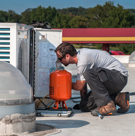 Service technician performing diagnosis and repair of a commercial HVAC unit.