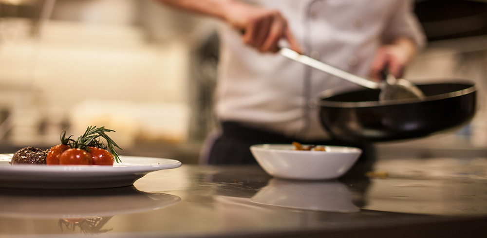 Close up of professional chef preparing and plating meals in a commercial kitchen.