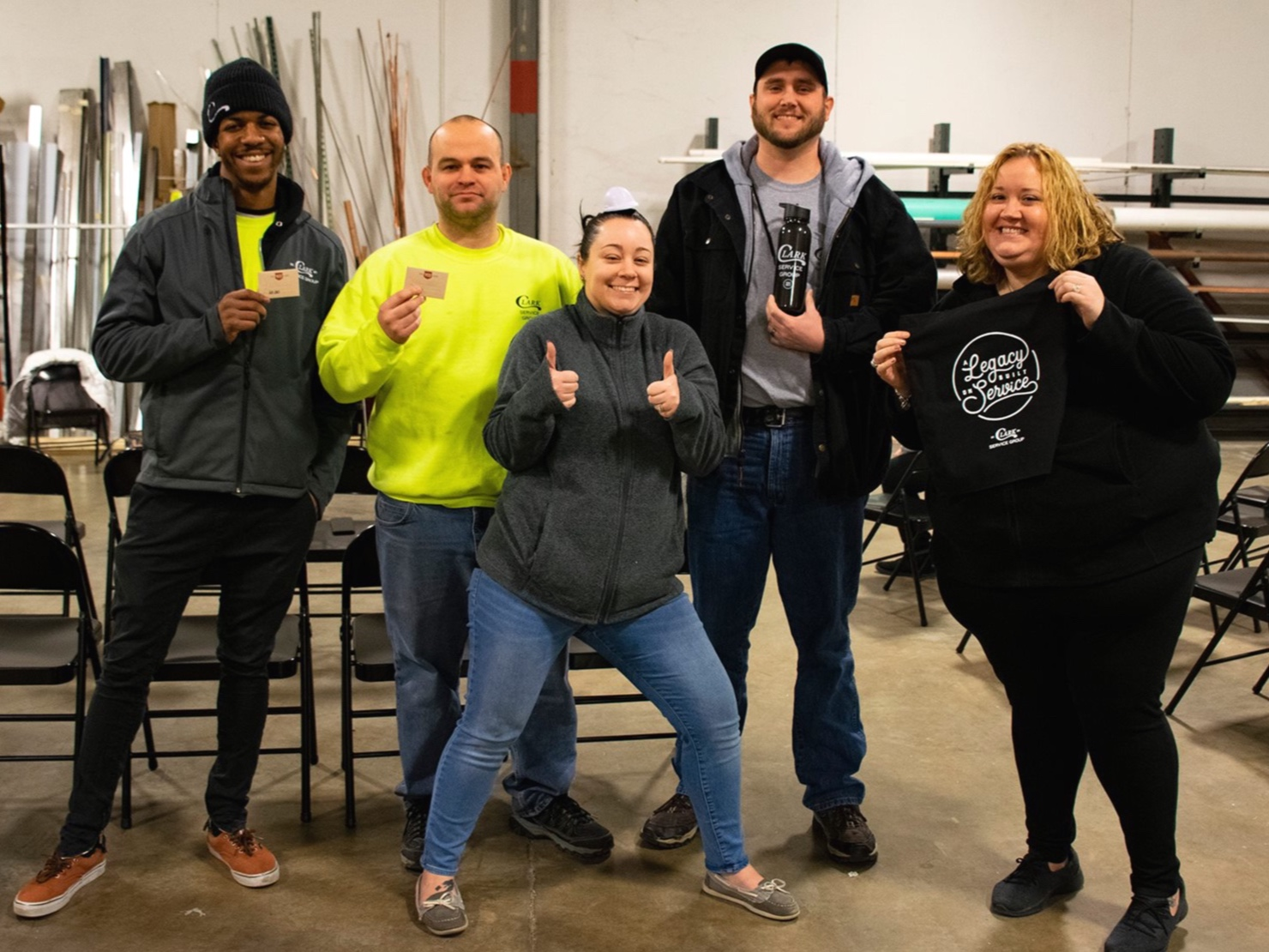 Clark Service Group employees smiling and giving thumbs up, holding branded SWAG.