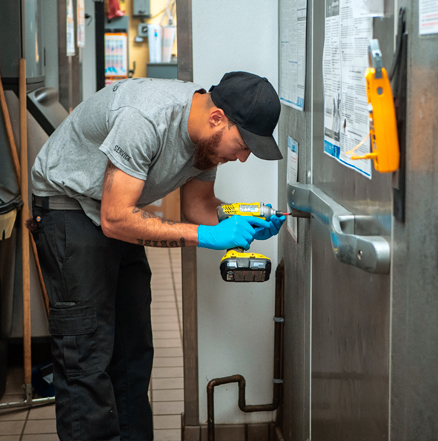 Service technician repairing the door to a refrigeration or freezer unit.