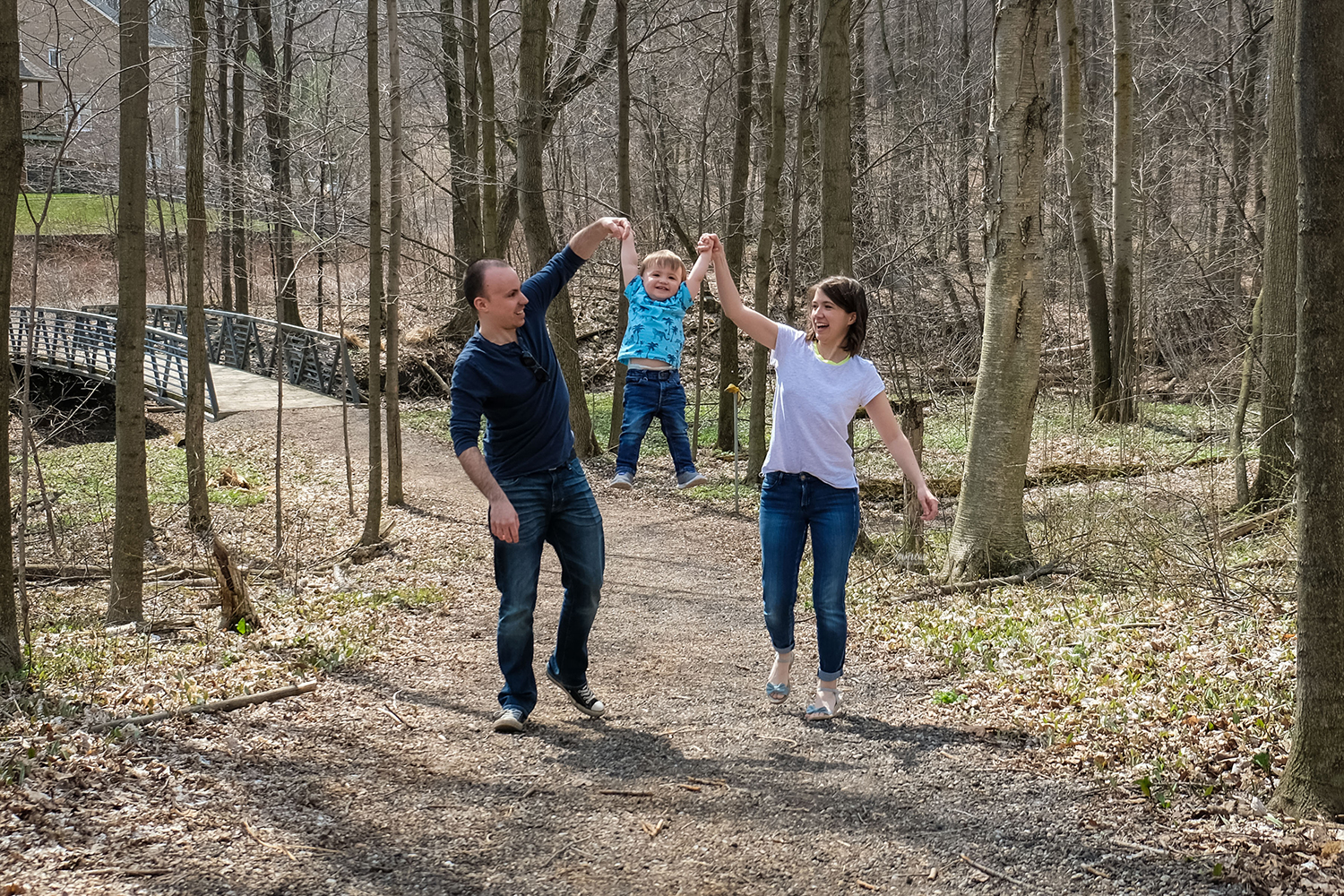 Happy parents swinging a grinning child by the arms on a forest trail Kitchener-Waterloo family photography