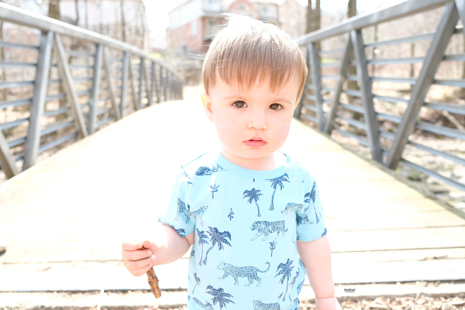 Child at the end of a walking bridge on a sunny day looking serious Family photography Kitchener-Waterloo