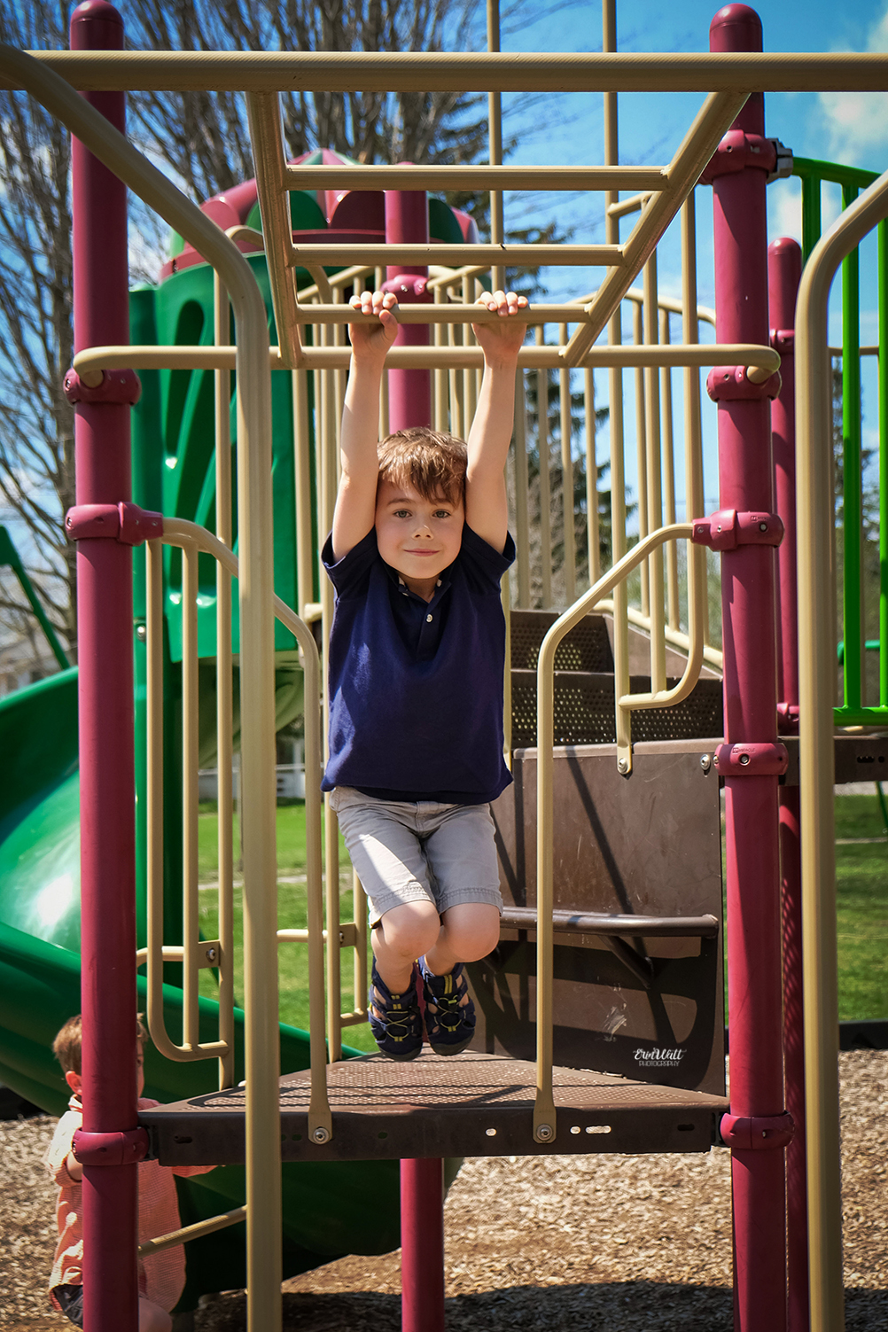Boy holding on to monkey bars outside on a sunny day family photography Kitchener-Waterloo