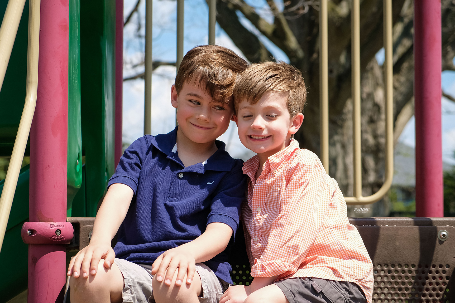 Two young brothers smiling at each other on a playground outside on a sunny day Family photography Kitchener-Waterloo