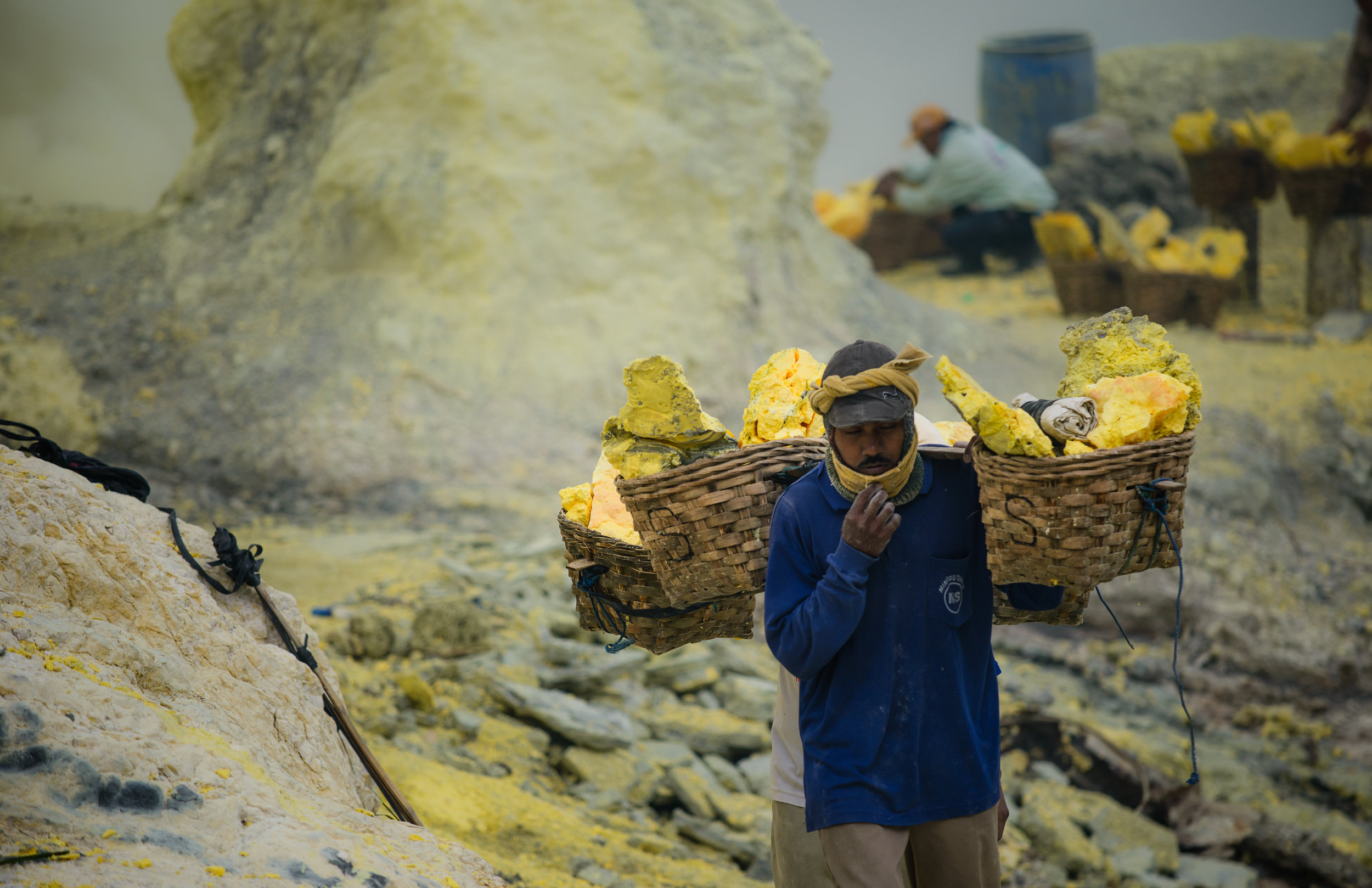 Into the lungs of hell - Human beings go to great lengths to make a living. The miners of Kawah Ijen climb up and down the crater of the active volcano several times a day to dig out sulphur. They breath in its lung-burning fumes and they load up to 90kg of sulphur into the baskets that they will proceed to carry on their shoulders all the way back to the delivery spot.